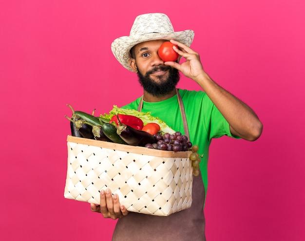 Jovem jardineiro afro-americano satisfeito com um chapéu de jardinagem, segurando uma cesta de vegetais, mostrando um gesto de olhar com tomate