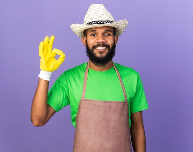 Jovem jardineiro afro-americano sorridente com chapéu de jardinagem e luvas mostrando um gesto de ok isolado na parede azul