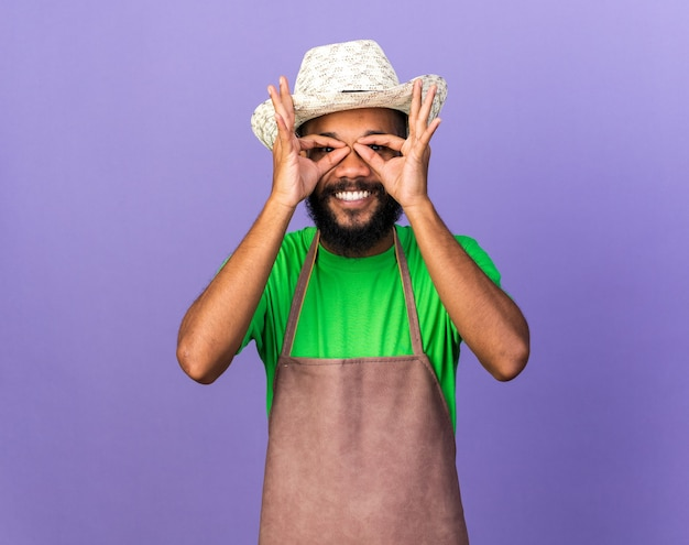 Jovem jardineiro afro-americano sorridente com chapéu de jardinagem mostrando gesto de olhar isolado na parede azul