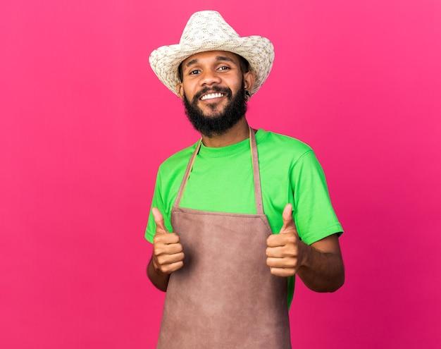 Jovem jardineiro afro-americano sorridente com chapéu de jardinagem mostrando os polegares para cima