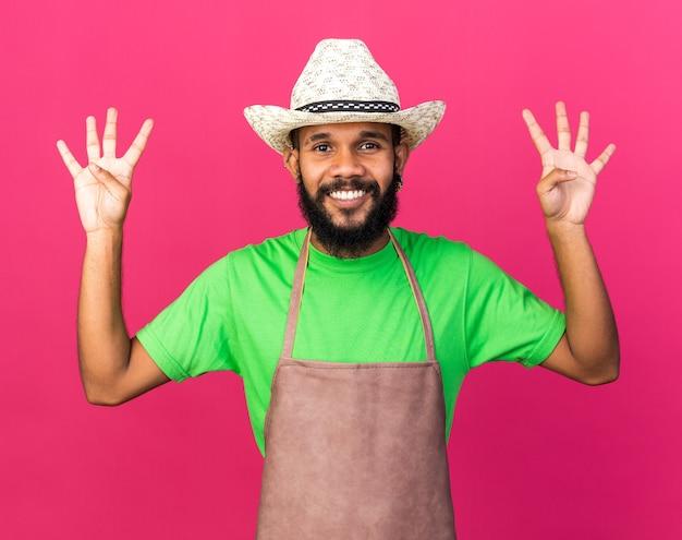 Jovem jardineiro afro-americano sorridente com chapéu de jardinagem mostrando quatro isolados na parede rosa