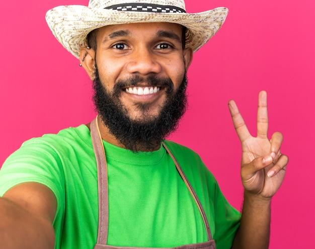 Jovem jardineiro afro-americano sorridente com chapéu de jardinagem, mostrando um gesto de paz isolado na parede rosa