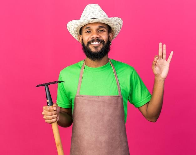Jovem jardineiro afro-americano sorridente com chapéu de jardinagem segurando o ancinho e mostrando um gesto de ok isolado na parede rosa