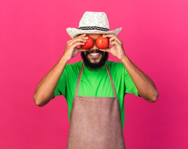 Jovem jardineiro afro-americano sorridente com chapéu de jardinagem segurando tomate e mostrando gesto de olhar isolado na parede rosa