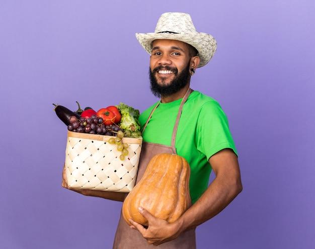 Jovem jardineiro afro-americano sorridente com chapéu de jardinagem segurando uma cesta de vegetais com abóbora isolada na parede azul