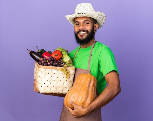 Jovem jardineiro afro-americano sorridente com chapéu de jardinagem segurando uma cesta de vegetais com abóbora