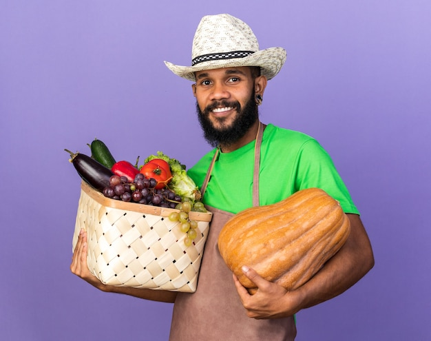 Jovem jardineiro afro-americano sorridente, usando um chapéu de jardinagem, segurando uma abóbora com uma cesta de vegetais