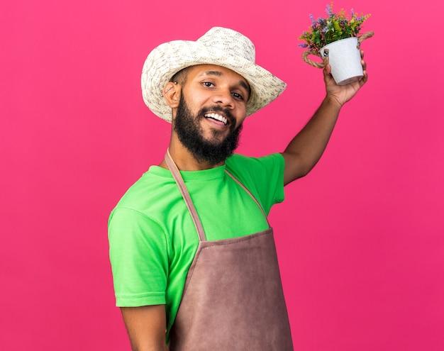 Jovem jardineiro afro-americano sorridente, usando um chapéu de jardinagem, segurando uma flor em um vaso de flores atrás, isolado na parede rosa