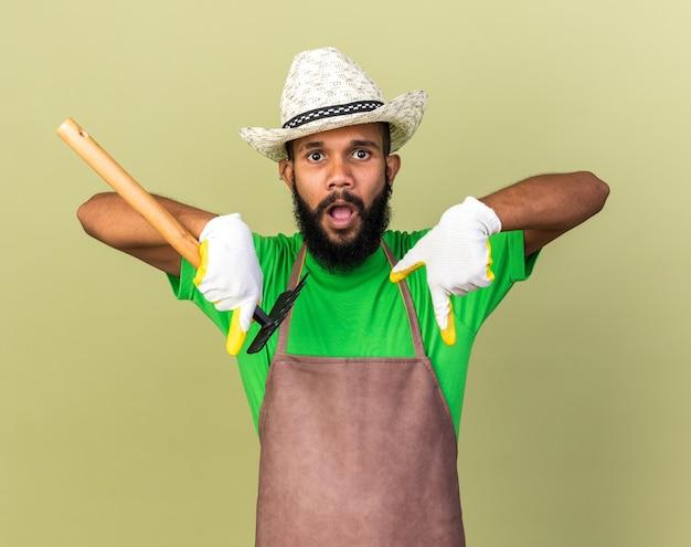 Jovem jardineiro afro-americano surpreso com chapéu de jardinagem e luvas segurando um ancinho isolado na parede verde oliva