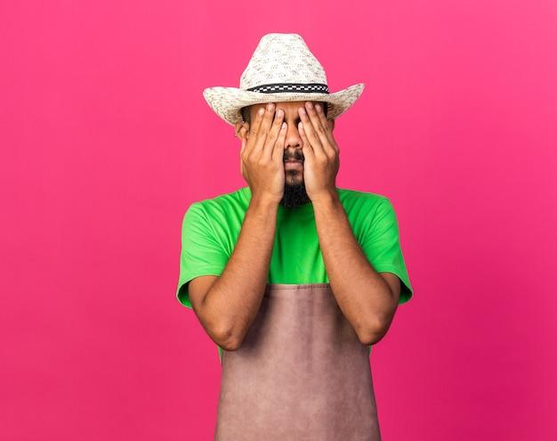 Jovem jardineiro afro-americano usando chapéu de jardinagem e cobrindo o rosto com as mãos
