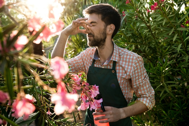 Jovem jardineiro alegre bonito cobrindo o nariz do cheiro com os dedos