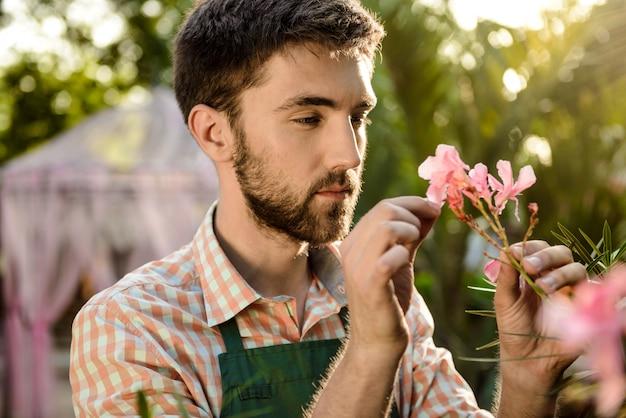 Jovem jardineiro alegre bonito sorrindo, cuidando de flores