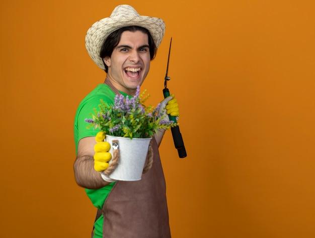 Jovem jardineiro alegre de uniforme usando chapéu de jardinagem e luvas segurando uma tesoura e segurando uma flor em um vaso