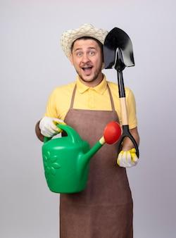 Jovem jardineiro alegre vestindo macacão e chapéu em luvas de trabalho segurando um regador e uma pá, sorrindo com uma cara feliz