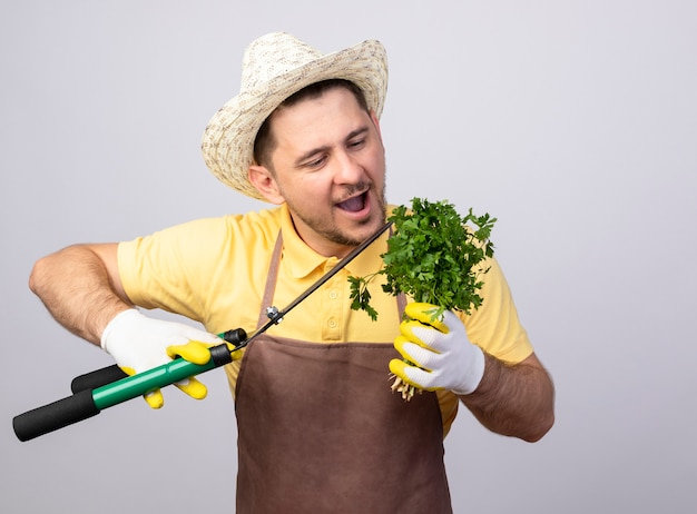 Jovem jardineiro alegre vestindo macacão e chapéu em luvas de trabalho segurando uma tesoura de sebes e ervas frescas sorrindo alegremente