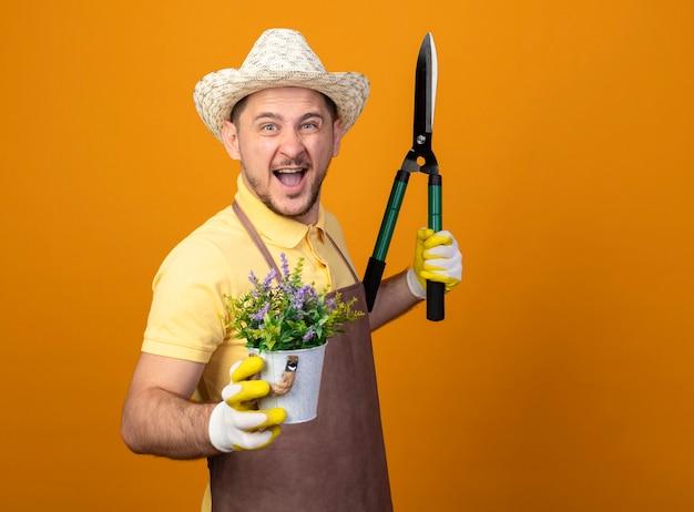 Jovem jardineiro alegre vestindo macacão e chapéu segurando uma tesoura de sebes e um vaso de plantas sorrindo, feliz e animado