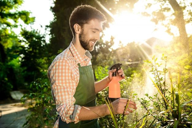 Jovem jardineiro bonito sorrindo, regando, cuidando das plantas