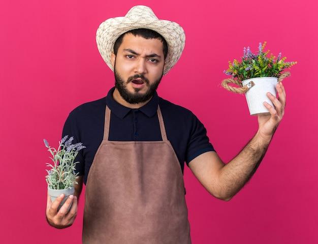 Jovem jardineiro caucasiano descontente com um chapéu de jardinagem segurando vasos de flores isolados na parede rosa com espaço de cópia
