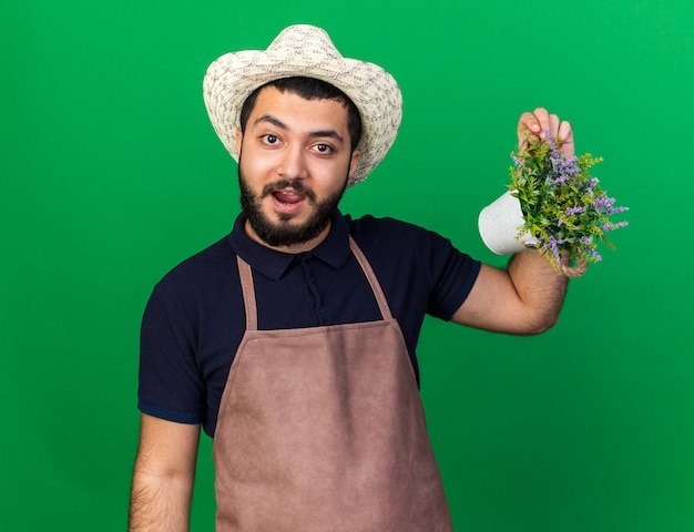 Jovem jardineiro caucasiano impressionado usando um chapéu de jardinagem segurando um vaso de flores isolado na parede verde com espaço de cópia