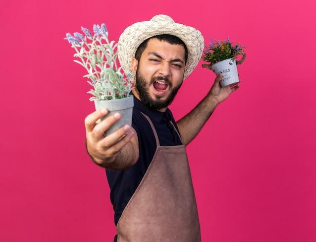 Jovem jardineiro caucasiano irritado com chapéu de jardinagem segurando vasos de flores isolados na parede rosa com espaço de cópia