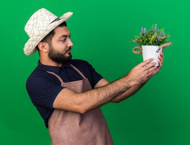 Jovem jardineiro caucasiano sem noção usando chapéu de jardinagem, segurando e olhando para um vaso de flores isolado em uma parede verde com espaço de cópia