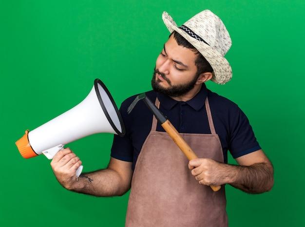 Jovem jardineiro caucasiano sem noção usando chapéu de jardinagem segurando o ancinho e olhando para o alto-falante isolado na parede verde com espaço de cópia