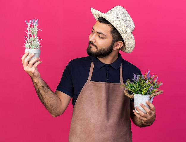 Jovem jardineiro caucasiano sem noção usando chapéu de jardinagem segurando vasos de flores isolados na parede rosa com espaço de cópia
