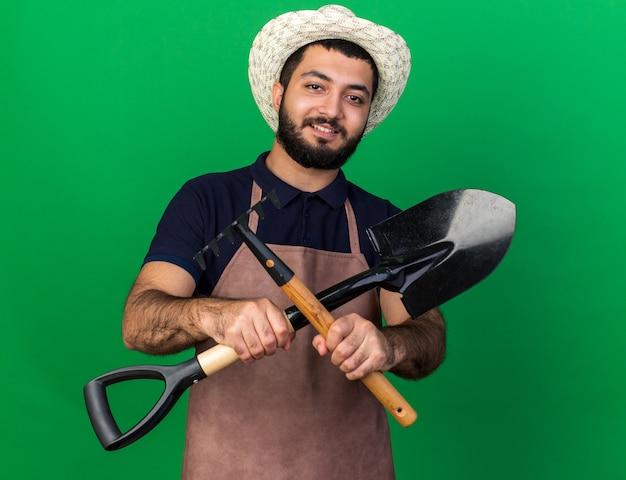 Jovem jardineiro caucasiano, sorridente, usando chapéu de jardinagem, segurando o ancinho e a pá de cruzamento isolados na parede verde com espaço de cópia