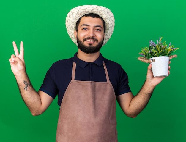 Jovem jardineiro caucasiano, sorridente, usando chapéu de jardinagem, segurando um vaso de flores e gesticulando o sinal da vitória, isolado na parede verde com espaço de cópia