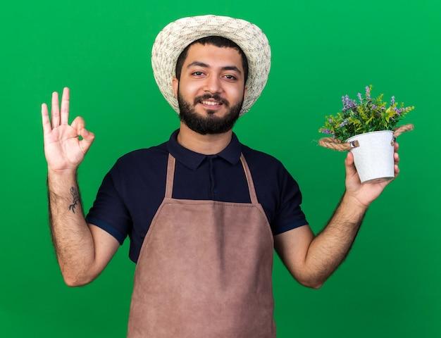 Jovem jardineiro caucasiano sorridente, usando chapéu de jardinagem, segurando um vaso de flores e gesticulando um sinal de ok isolado na parede verde com espaço de cópia