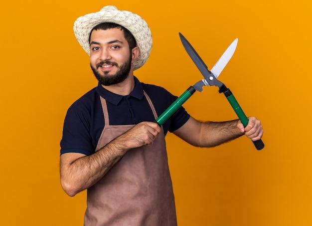 Jovem jardineiro caucasiano, sorridente, usando chapéu de jardinagem, segurando uma tesoura de jardinagem e parecendo isolado em uma parede laranja com espaço de cópia