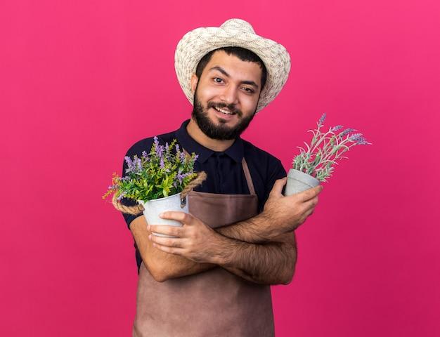 Jovem jardineiro caucasiano, sorridente, usando chapéu de jardinagem, segurando vasos de flores, cruzando os braços isolados na parede rosa com espaço de cópia