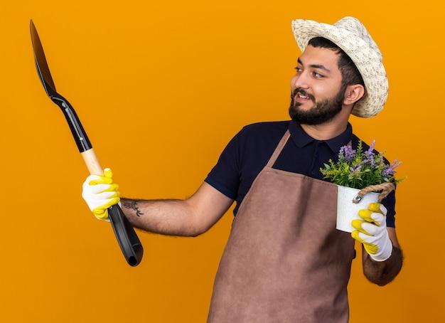 Jovem jardineiro caucasiano, sorridente, usando luvas e chapéu de jardinagem, segurando um vaso de flores e olhando para uma pá isolada na parede laranja com espaço de cópia