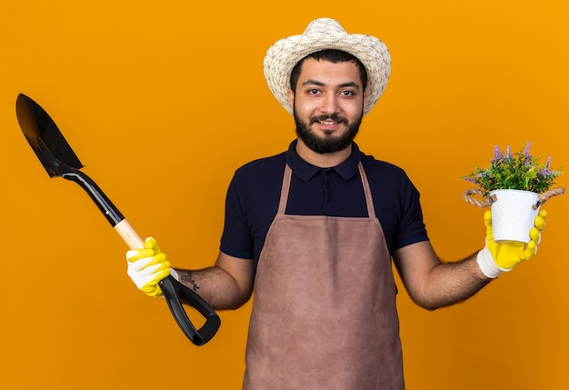 Jovem jardineiro caucasiano, sorridente, usando luvas e chapéu de jardinagem, segurando uma pá e um vaso de flores isolados na parede laranja com espaço de cópia