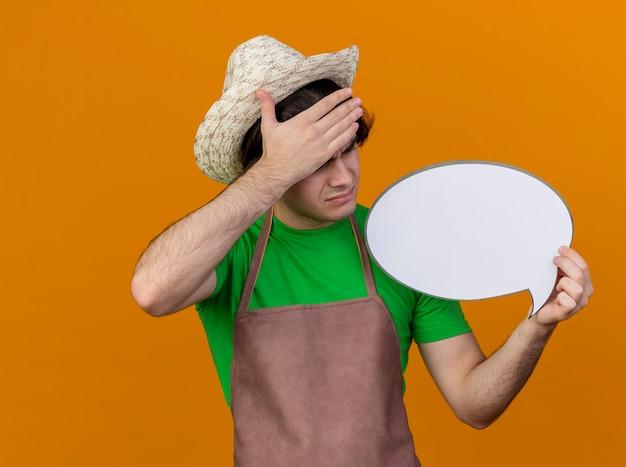 Jovem jardineiro chateado de avental e chapéu segurando um cartaz de balão de fala em branco, olhando para ele com a mão na cabeça, ficando confuso e decepcionado em pé sobre um fundo laranja