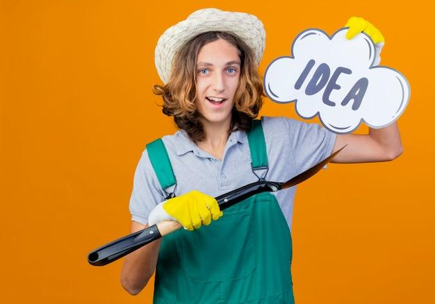Jovem jardineiro com luvas de borracha e macacão segurando uma pá e um balão de fala