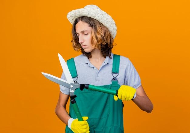 Jovem jardineiro com luvas de borracha, macacão e chapéu, segurando um cortador de cerca viva