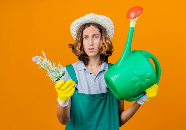 Jovem jardineiro com luvas de borracha, macacão e chapéu, segurando um regador
