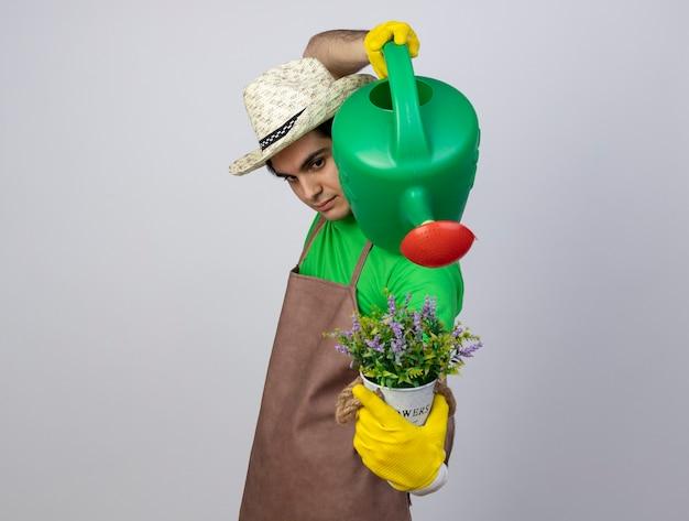 Jovem jardineiro confiante de uniforme, usando chapéu de jardinagem e luvas, regando as flores em um vaso de flores com um regador