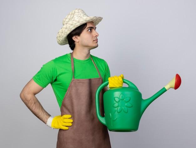 Jovem jardineiro confiante de uniforme, usando chapéu de jardinagem, olhando para o lado, segurando o regador e colocando a mão no quadril