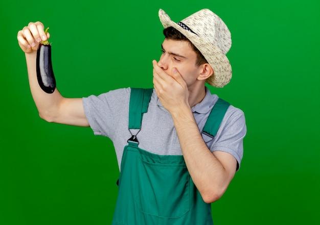 Jovem jardineiro confiante usando chapéu de jardinagem e colocando a mão na boca, segurando e olhando para uma berinjela