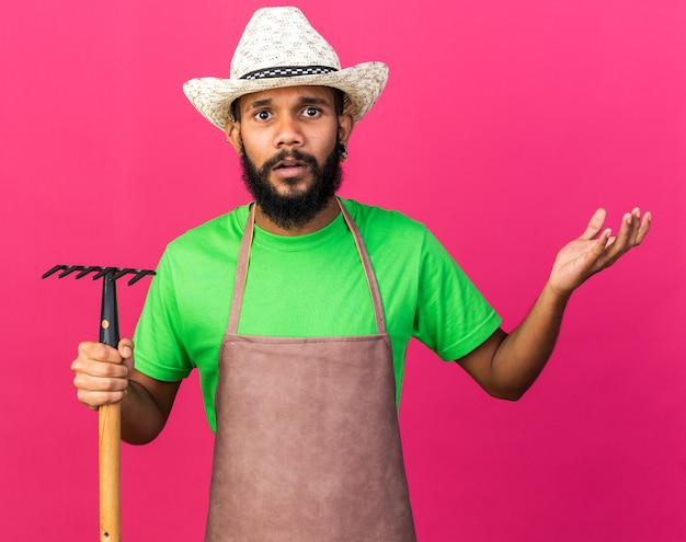 Jovem jardineiro confuso, afro-americano, usando um chapéu de jardinagem, segurando o ancinho, estendendo a mão