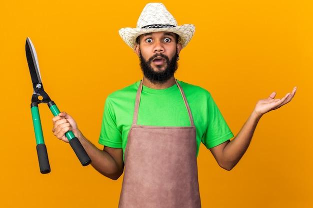 Jovem jardineiro confuso, afro-americano, usando um chapéu de jardinagem, segurando uma tesoura, estendendo a mão isolada na parede laranja
