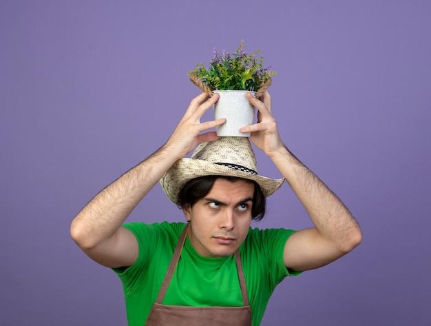 Jovem jardineiro confuso de uniforme usando chapéu de jardinagem segurando uma flor em um vaso de flores na cabeça