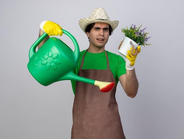 Jovem jardineiro confuso de uniforme, usando um chapéu de jardinagem e luvas, segurando um regador com uma flor em um vaso