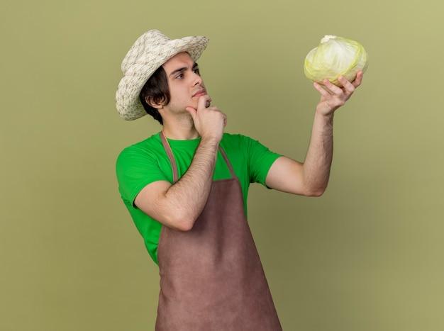 Jovem jardineiro de avental e chapéu segurando repolho olhando intrigado de pé sobre um fundo claro