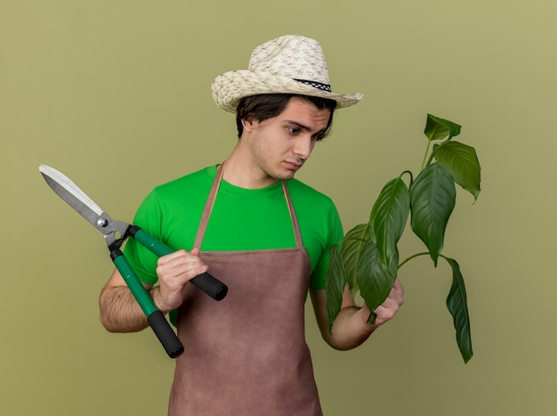 Jovem jardineiro de avental e chapéu segurando uma planta e um cortador de cerca viva olhando para ela com uma cara séria em pé sobre um fundo claro