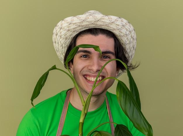 Jovem jardineiro de avental e chapéu segurando uma planta olhando para a câmera com um sorriso no rosto em pé sobre um fundo claro