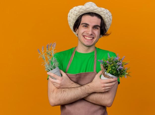 Jovem jardineiro de avental e chapéu segurando vasos de plantas e sorrindo alegremente com as mãos cruzadas em pé sobre a parede laranja
