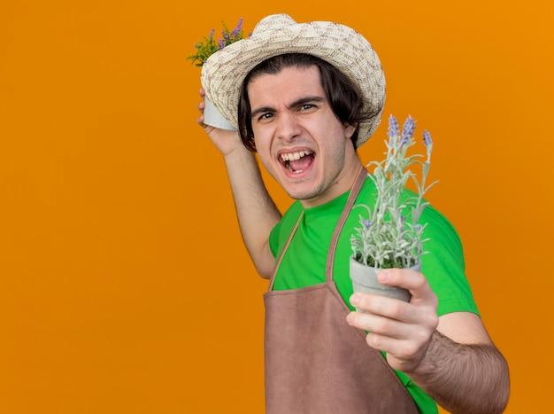 Jovem jardineiro de avental e chapéu segurando vasos de plantas, parecendo gritando com uma cara brava enlouquecendo de pé sobre uma parede laranja